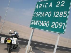 Motorcycle at Road Sign saying Santiago 2091 kms