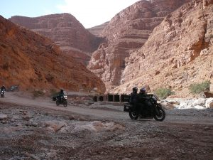 Motorcycles riding through dramatic cliffs of Todra Gorge Morocco